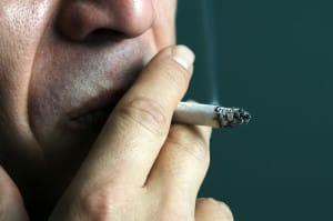 Man Smoking Cigarette Unaware of Oral Health Problems Caused by Tobacco
