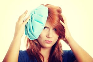 Red Haired Woman Uses Hot Compress to Relieve TMJ Pain in Temple