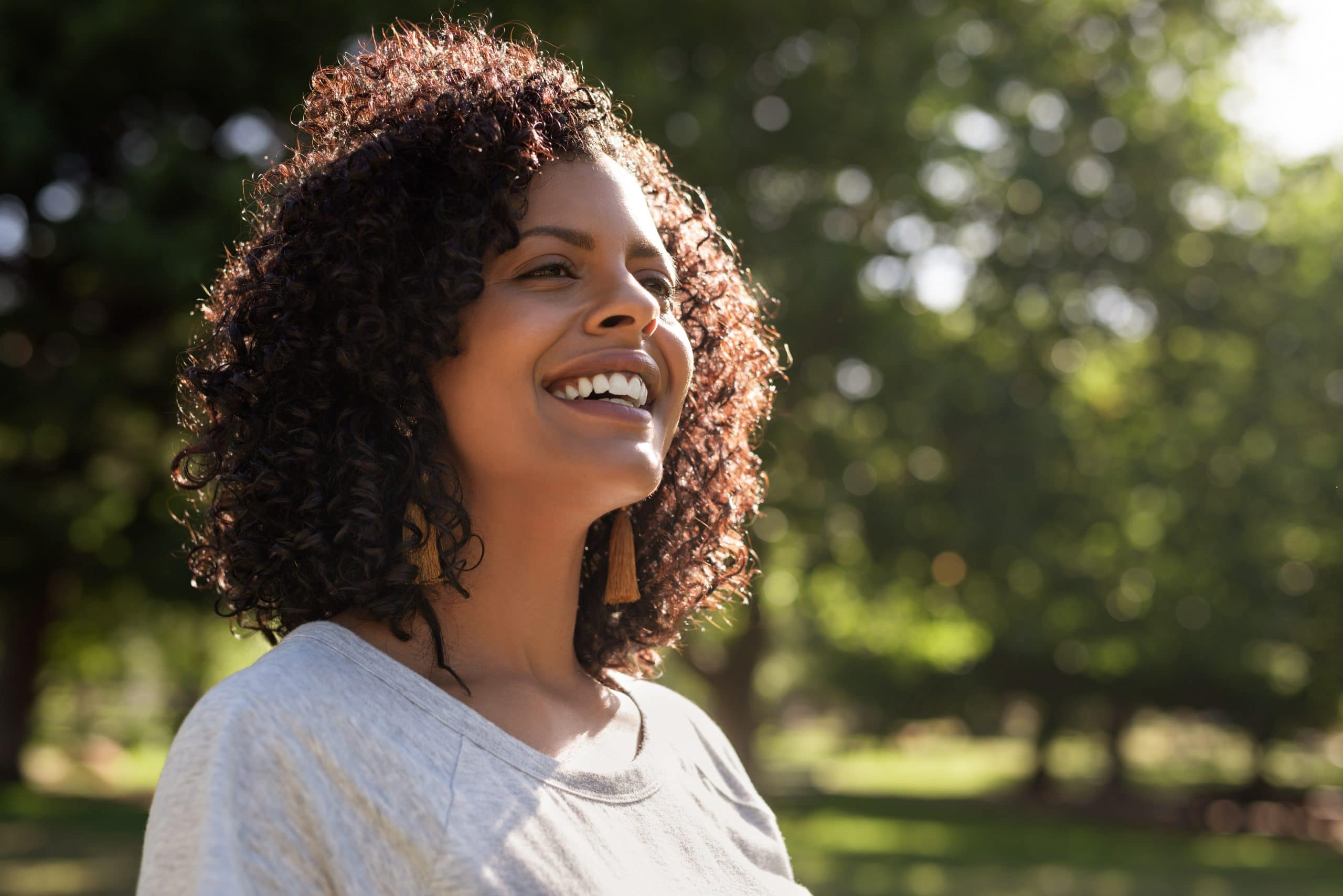 Young woman with curly hair smiling while standing outside in a park on a sunny summer afternoon