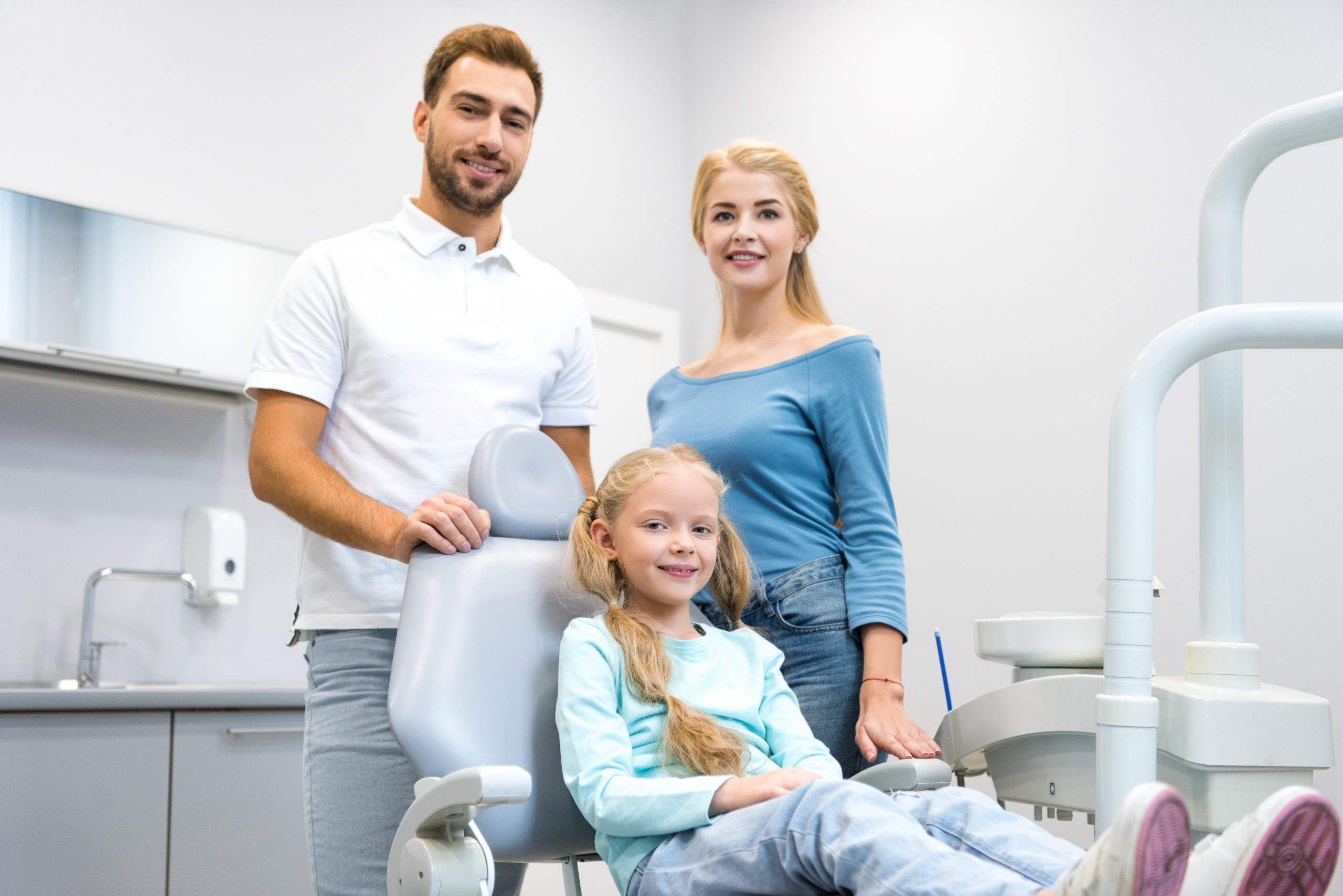 happy young family looking at camera at dentist office