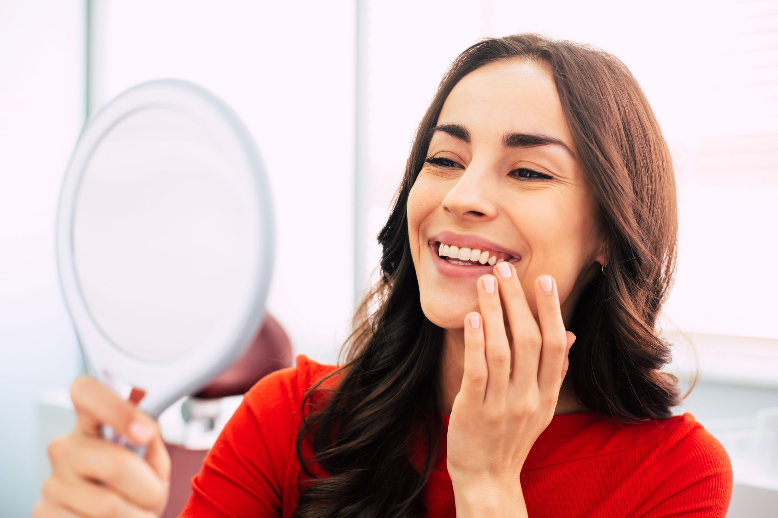 Honed to perfection. Fabulous woman clothed in red sweater, with curly long hair and elegant hands is holding a mirror for looking through the final work of dental doctor.