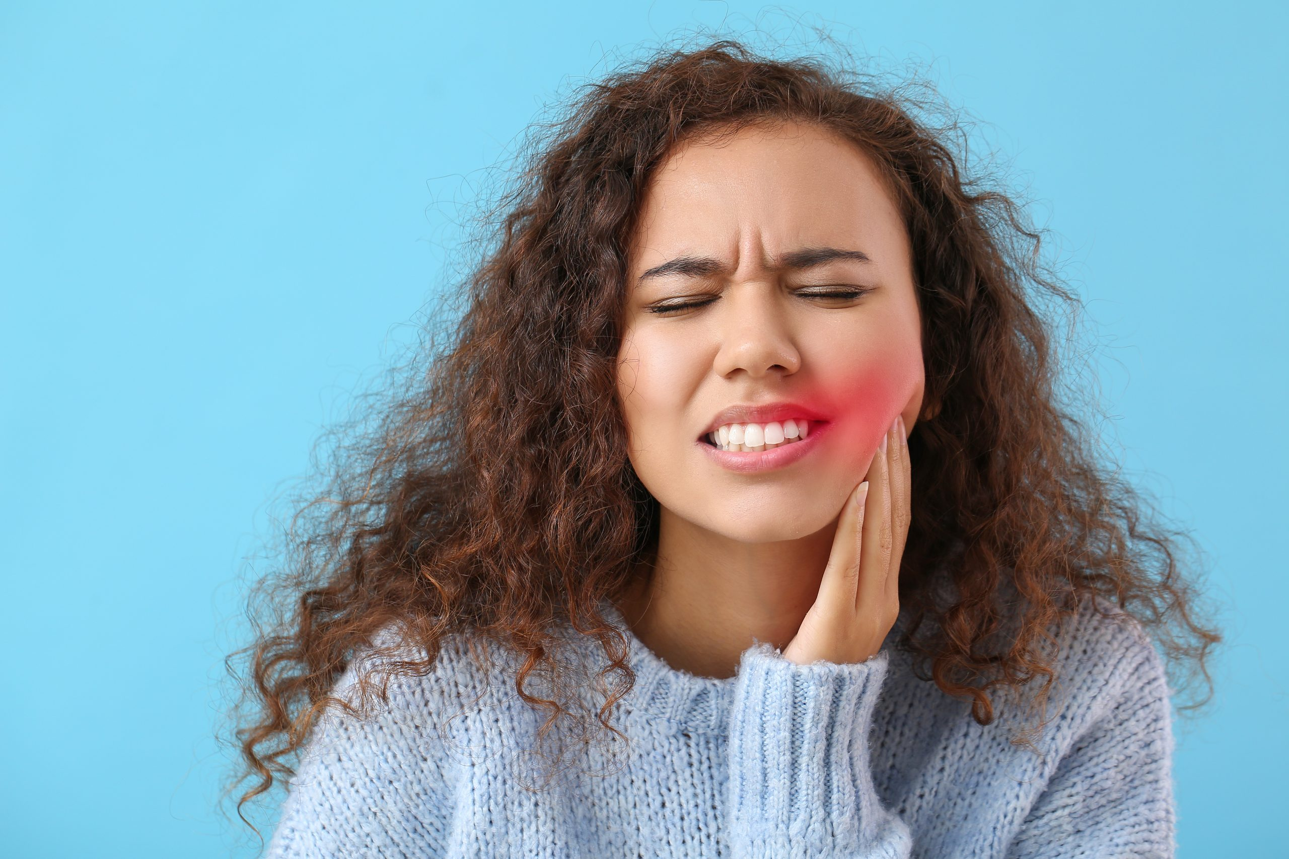 African-American woman suffering from tooth ache on color background