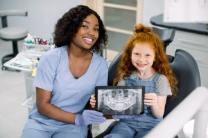 Little smiling girl with red curly hair sitting on chair and looking at camera, while holding x-ray scan image of her teeth on digital tablet together with her cheerful black female dentist at clinic.