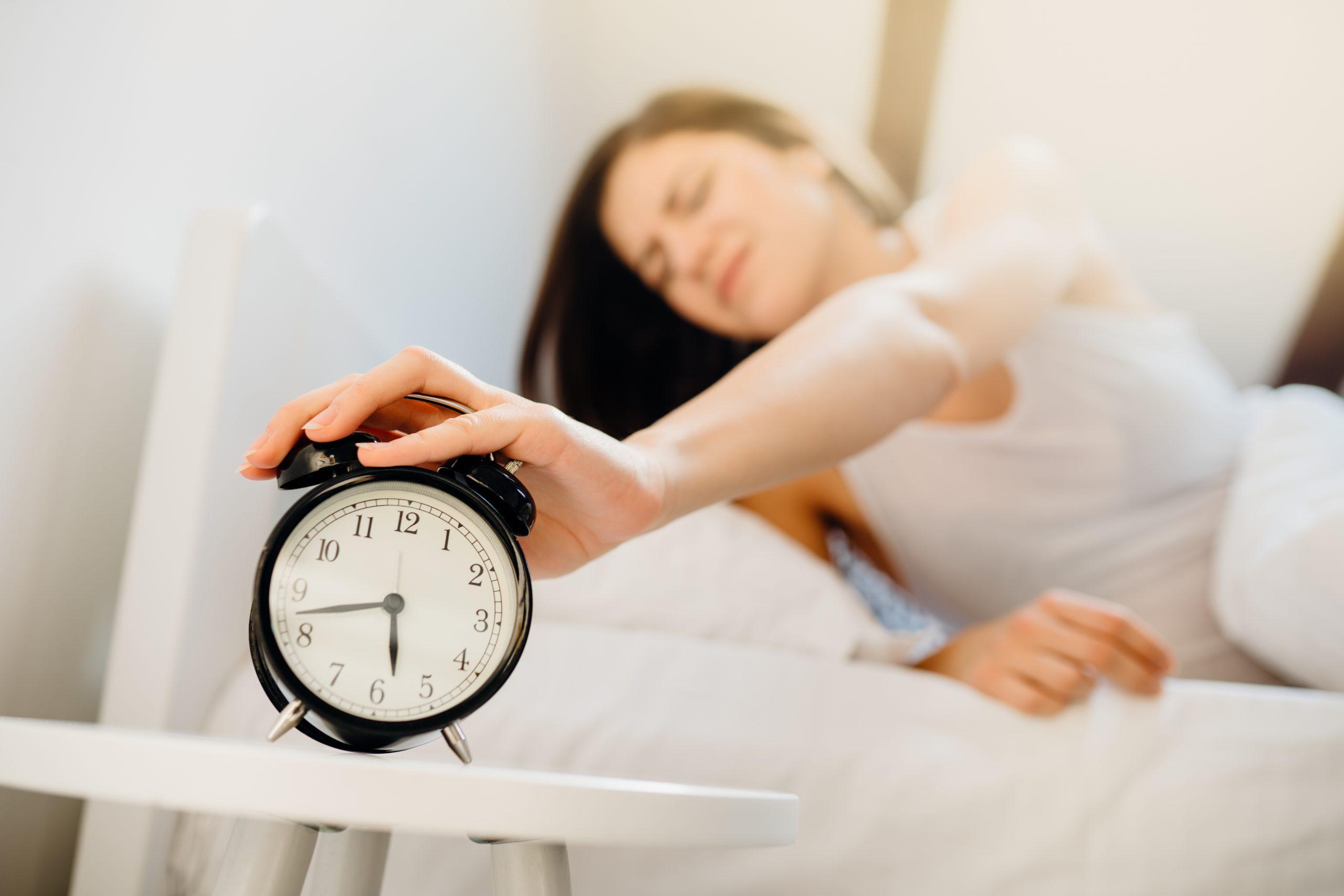 Alarm clock ringing.Woman waking up in early morning for work.Sleeping disorder.Tired woman oversleeping,bad sleep quality.Sleep deprived mom.Waking inertia,bad mood after dreaming nightmares.Insomnia