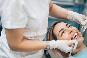 Professional doctor dentist examine and treat spoiled teeth with the use of special dental instruments, medical equipments.