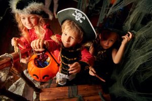 Happy children in carnival costumes trick or treating with pumpkin basket in the old wooden house. Halloween party.
